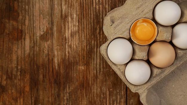 Witte eieren karton en gebarsten ei helft met dooier bovenaanzicht op houten achtergrond. pasen en gezond eten ontbijt koken concept
