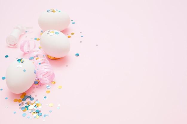 Witte eieren op een roze achtergrond, feestelijke schittert, met kopie ruimte. pasen concept.