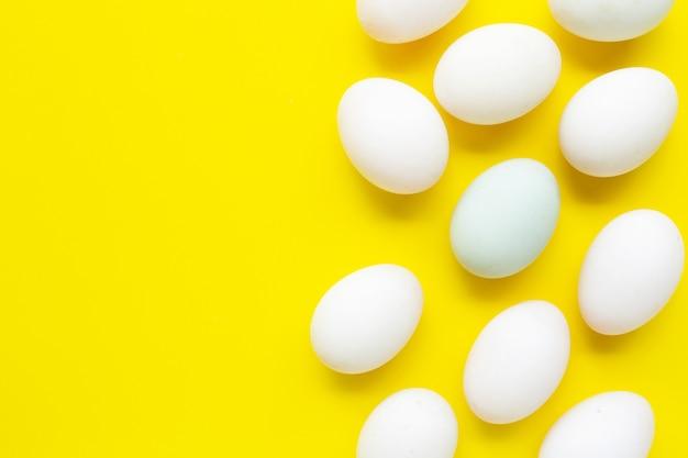 Witte eieren op gele achtergrond.