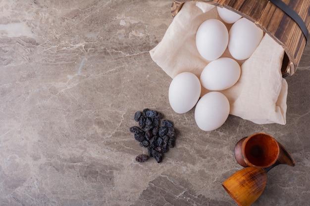 Witte eieren uit een houten emmer