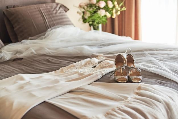 Witte elegante huwelijkskleding en schoenen die op het bed liggen.