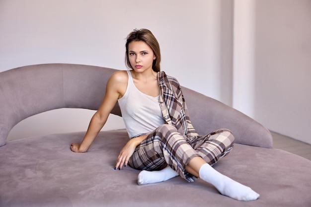 Witte elegante vrouw in pyjama zit op bed