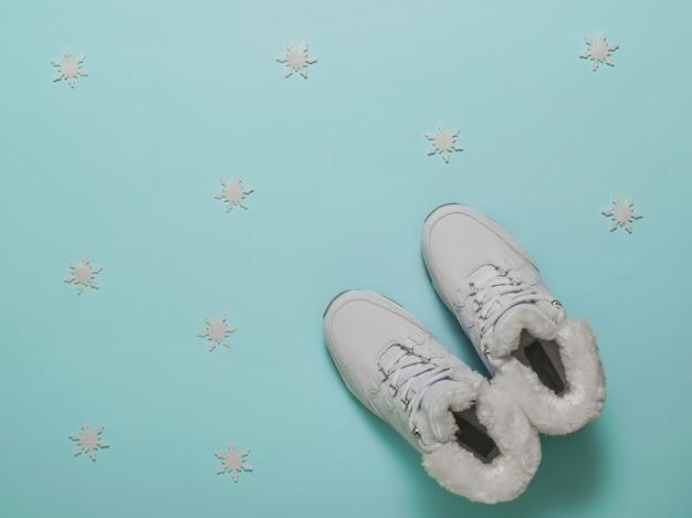 Witte elegante warme sportschoenen voor dames op een blauwe achtergrond.