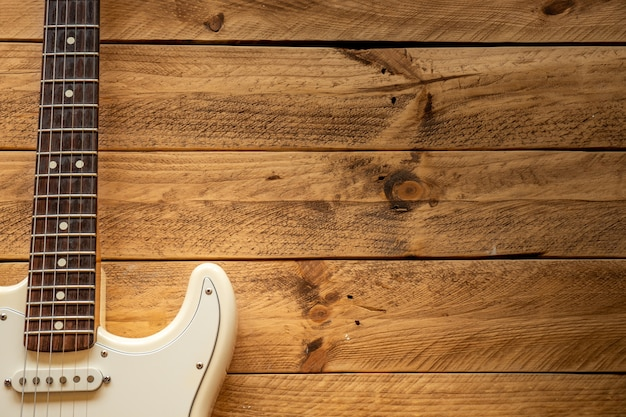 Witte elektrische gitaar op een bruin houten tafel, met kopie ruimte.