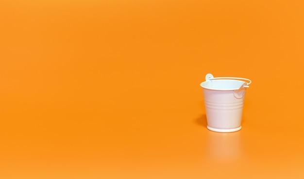 Witte emmer op oranje achtergrond, minimalismeconcept