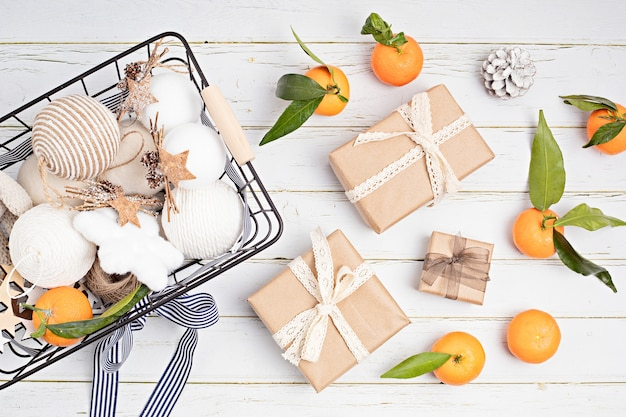 Witte en beige kerst ornamenten in mand met papier verpakt cadeautjes, mandarijnen en dennenappel op houten tafel. eco-vriendelijk zero waste xmas shopping concept. plat lag, bovenaanzicht.
