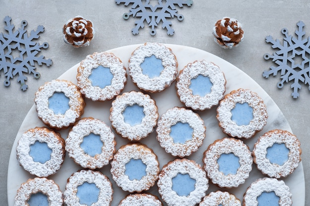 Witte en blauwe bloem linzer-koekjes op lichte steenoppervlakte met de winterdecoratie