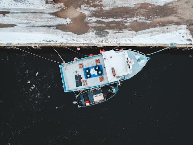 Witte en blauwe boot op kust overdag