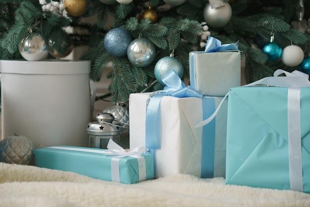 Witte en blauwe geschenkdozen met blauwe linten onder gedecoreerde kerstboom