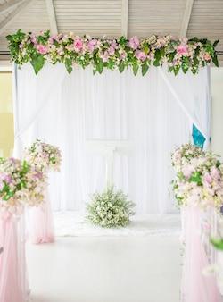 Witte en blauwe houten boog bij huwelijksceremonie met rij bruiloft stoelen versierd met witte en roze bloemen