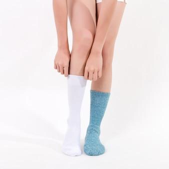 Witte en blauwe katoenen sokken op de voeten van de mooie vrouw