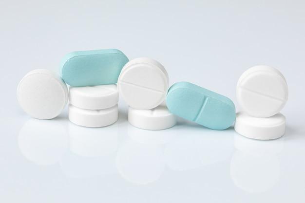 Witte en blauwe tabletten of pillen, medicatie of drugs .. apotheek, geneeskunde behandeling concept.