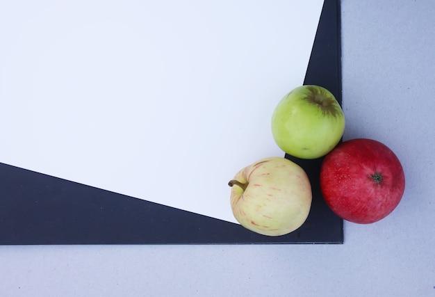 Witte en blauwe vellen papier met drie kleurrijke rijpe appels
