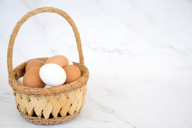 Witte en bruine eieren in rieten mand op marmeren achtergrond met exemplaarruimte. verse eieren van boerderijkippen. gelukkig pasen.
