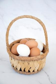 Witte en bruine eieren in rieten mand op marmeren achtergrond. verse natuurlijke eieren. gelukkig pasen.