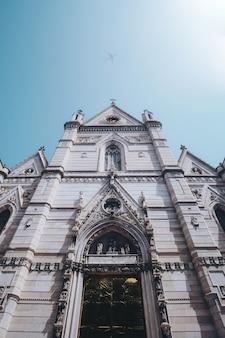 Witte en bruine kerk onder blauwe en witte luchten