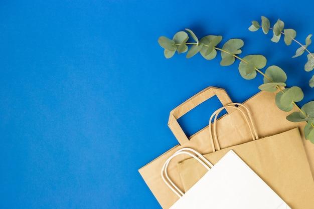 Witte en bruine papieren zakken met handvatten en eucalyptusbladeren op blauwe achtergrond.