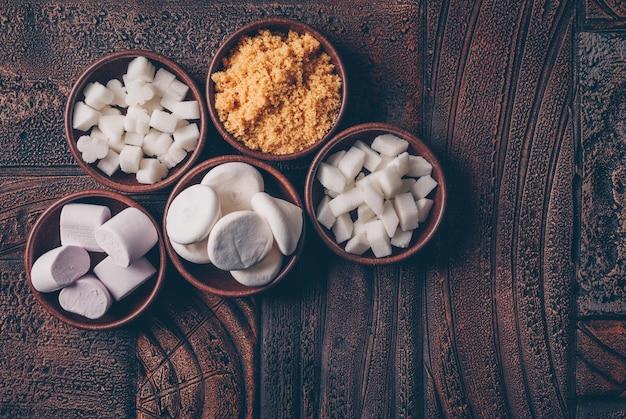 Witte en bruine suiker in kommen met snoepjes en marshmallow bovenaanzicht op een donkere houten tafel