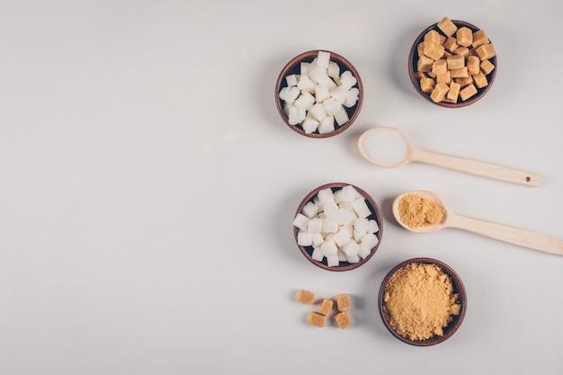 Witte en bruine suikerklontjes in kommen met lepels bovenaanzicht