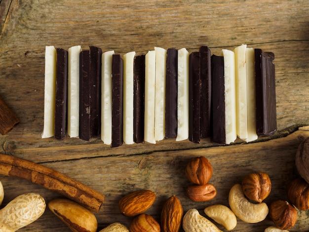 Witte en donkere chocolade opgesteld op een houten oppervlak. veel noten, rozijnen en kaneel.