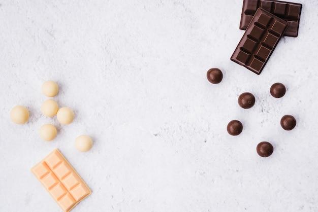 Witte en donkere chocoladereep en ballen op witte ruwe achtergrond