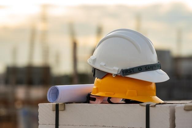 Witte en gele helm veiligheidshelm veiligheid in de bouw van de site, concept veiligheid eerst.