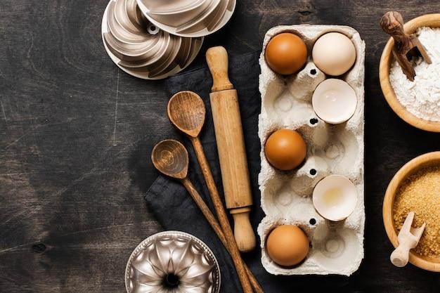 Witte en gele kippeneieren en schelpen in een oude vintage container van cellulose met bloem, suiker, houten lepels en een deegroller op een oude donkere houten