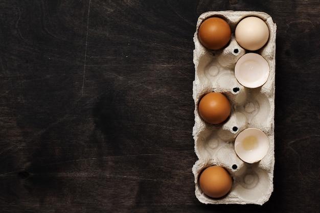 Witte en gele kippeneieren en schelpen in een oude vintage container van cellulose op een oude donkere houten