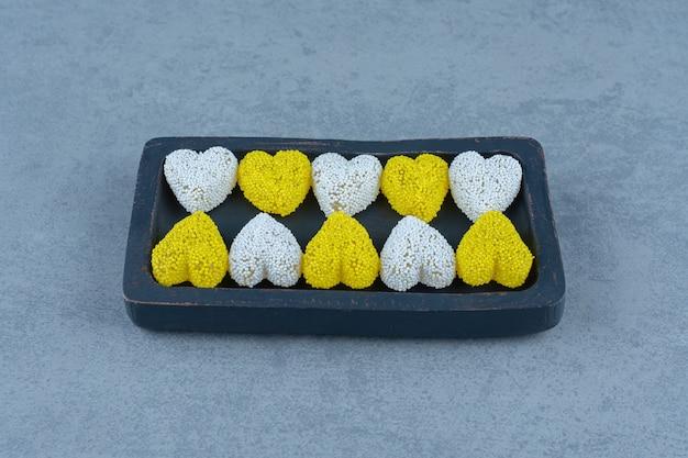 Witte en gele koekjes op het bord, op de marmeren tafel.