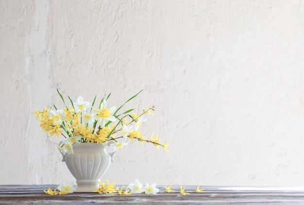 Witte en gele lentebloemen in vaas op oppervlakte oude witte muur