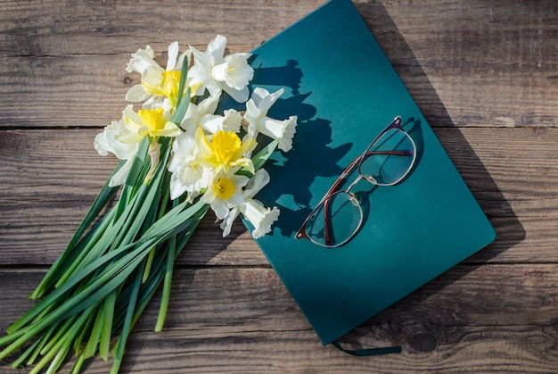 Witte en gele narcissen, boek en glazen op een houten tafel