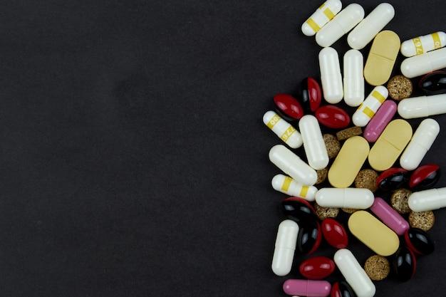 Witte en gele pillen, tabletten, vitamines, medicijnen, pillen en medicijnen verspreid op een donkere tafel. pillen voor behandeling en medicijnen.