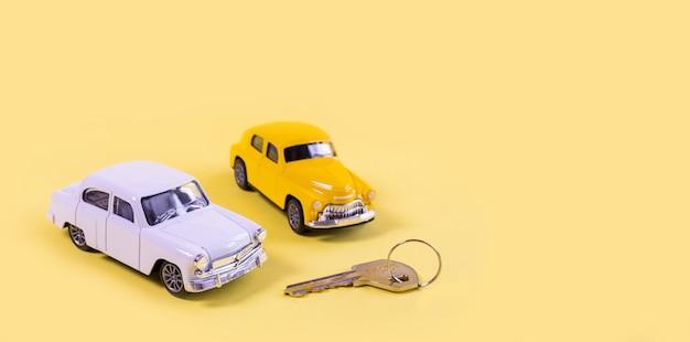 Witte en gele speelgoedauto's geïsoleerd op gele achtergrond
