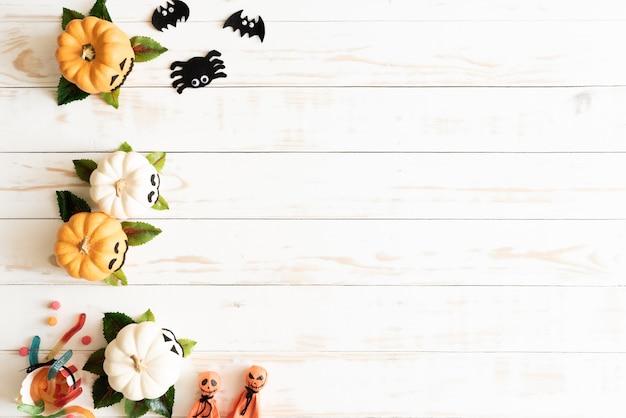 Witte en gele spookpompoenen met halloween-ambacht op witte houten achtergrond