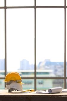 Witte en gele veiligheidshelm in bouwwerf, licht van groot raam op de achtergrond