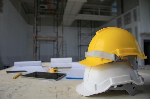 Witte en gele veiligheidshelm in bouwwerf, steiger op achtergrond