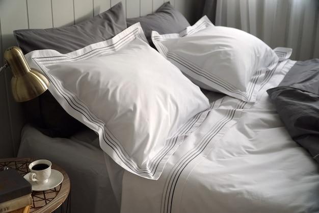 Witte en grijze kussens en deken op wit bed in ruime slaapkamer interieur.