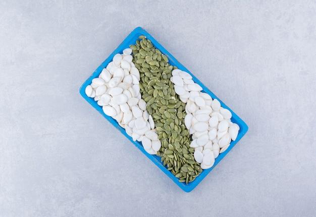 Witte en ongepelde groene pompoenpitten in een schaal op marmeren ondergrond