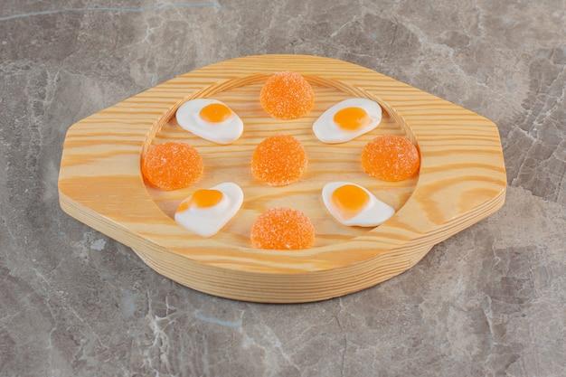 Witte en oranje snoepjes op houten plaat over grijs oppervlak.