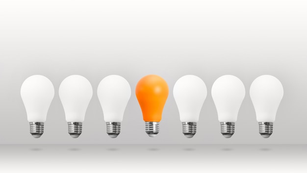Witte en oranje spaarlampen die op witte achtergrond vliegen. wees anders, out of the box denkconcept.