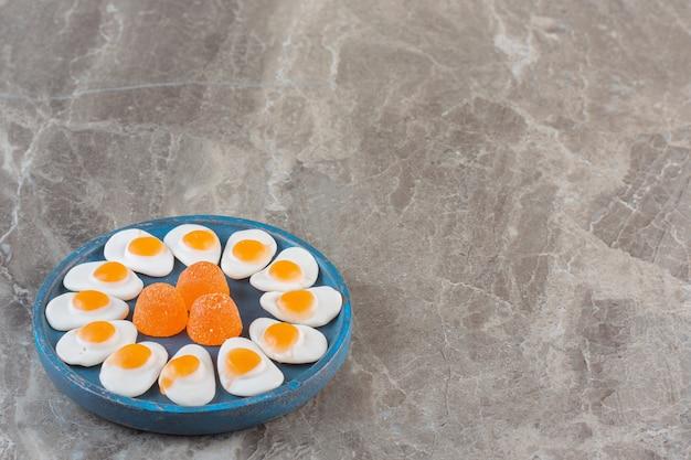 Witte en oranje zoete snoepjes. snoepjes op blauwe houten plaat.