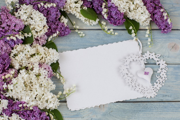 Witte en paarse seringen, lelietje-van-dalen, een vel papier en een hart