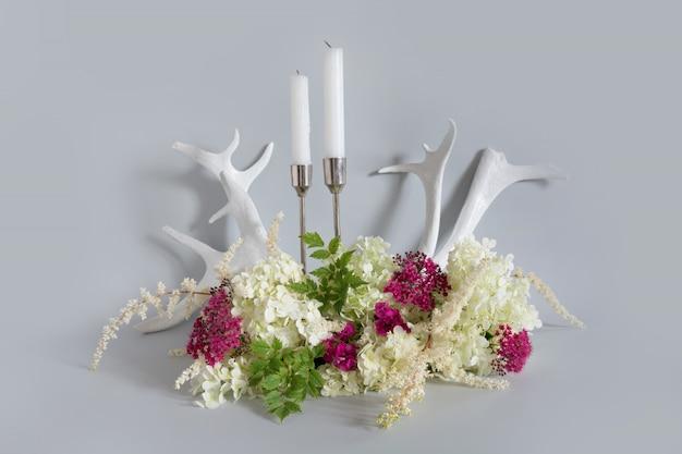 Witte en paarse wilde bloemen, kaars en rendiergewei op pastel grijs. samenstelling van de natuur.