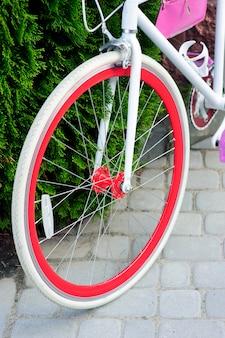 Witte en rode fiets. stijlvolle vrouwelijke rode fiets. buiten staan op een zonnige dag. goede pagode om te fietsen.