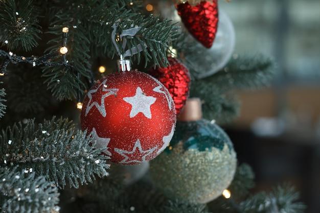 Witte en rode kerstmisballen van de close-up met een gouden slinger op kerstboomtakken.