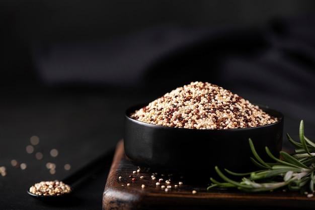 Witte en rode quinoagrutten in een zwarte kom Premium Foto