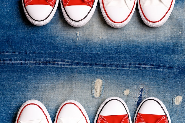 Witte en rode sneakers op de gescheurde denimachtergrond.