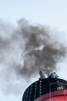 Witte en rode stoompijp met zwarte rook