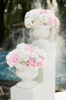 Witte en roze bloemen in vazen tijdens de huwelijksceremonie