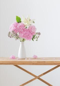 Witte en roze bloemen in witte vaas op houten plank